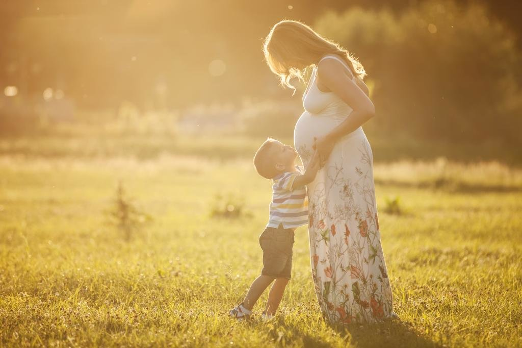 Ребенок целует животик маме